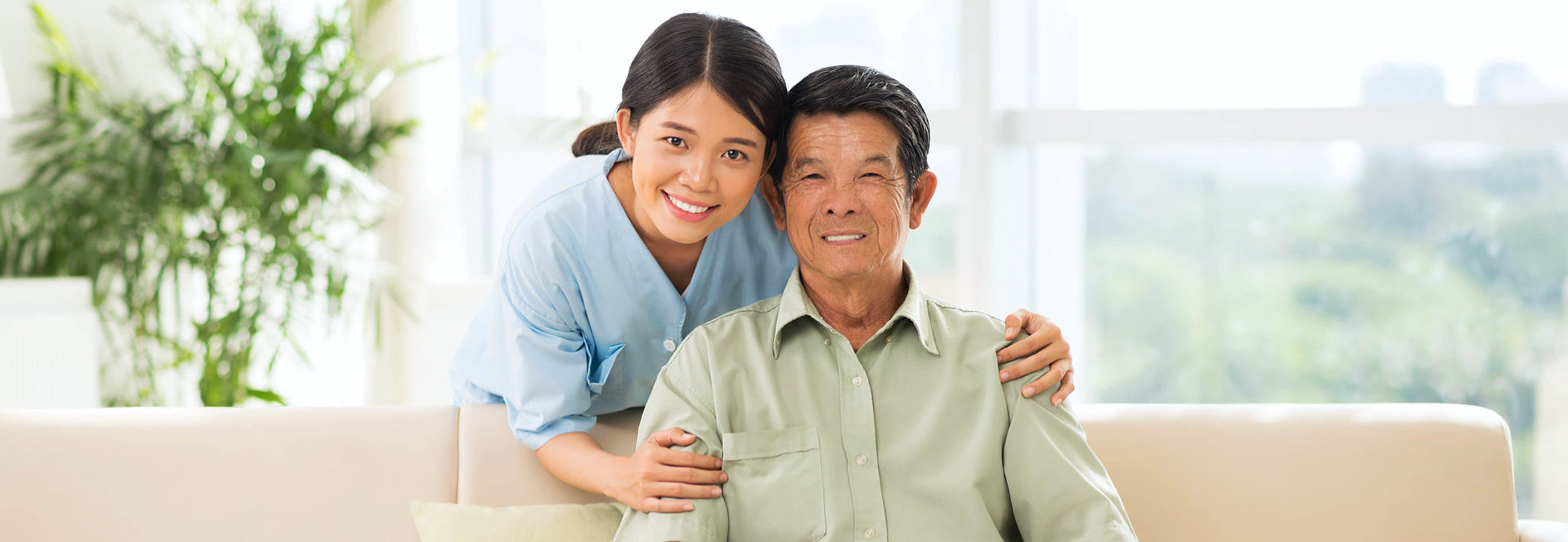 caregiver and elder man in couch smiling