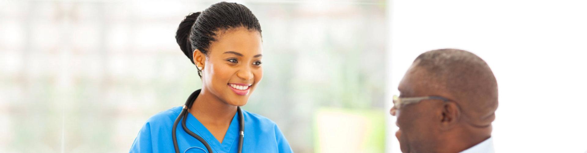 skilled nurse looking at the senior man while smiling